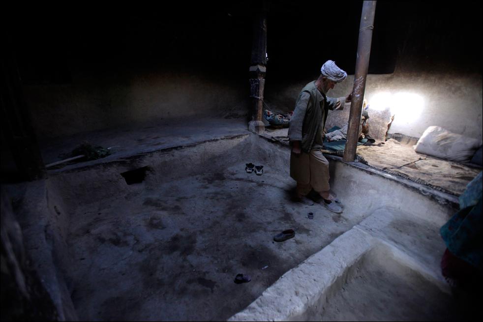 13. Житель деревни Сараб, опийный наркоман Ислам Бег обувается, чтобы пойти работать на картофельное поле после утреннего курения опиума в провинции Бадахшан, Афгнистан. «Я продал свою землю. И теперь работаю на ней. Я продал своих кур и коров», - говорит Бег, чья семья также зависима от опиума. (AP/Julie Jacobson)