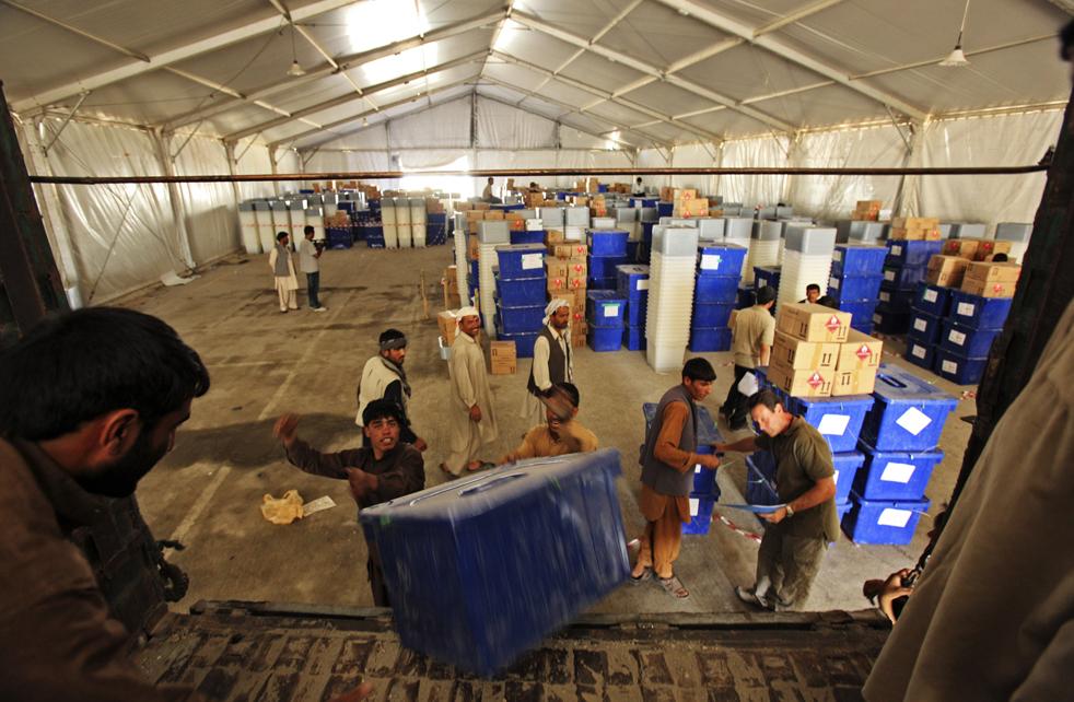 3) 3. Рабочие нагружают грузовики, направляющиеся к избирательным участкам, необходимыми для выборов материалами на территории Независимой Избирательной Комиссии в Кабуле, в воскресенье 16 августа. (AP/Dima Gavrysh)