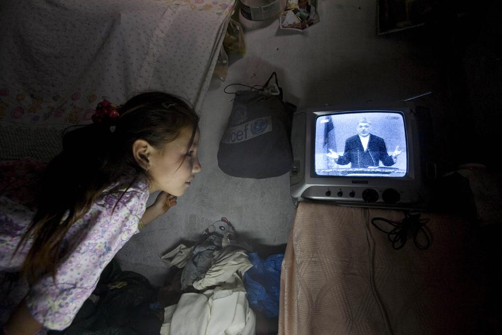 6) 6. Афганская девочка слушает речь кандидата в президенты Афганистана и нынешнего президента Хамида Казая по телевизору во время президентских дебатов, транслировавшихся в прямом эфире, в Кабуле, в воскресенье 16 августа. (AP/Farzana Wahidy)