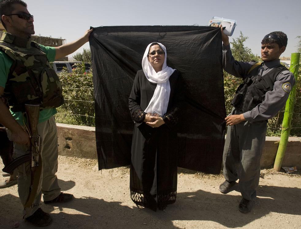 11) 11. Форозан Фана – единственная из двух представительниц слабого пола среди кандидатов в президенты – позирует для фотографии, пока ее охранники держат для нее черную материю во время предвыборной кампании в «Женском саду» в Кабуле, пятница 14 августа. (AP/Farzana Wahidy)