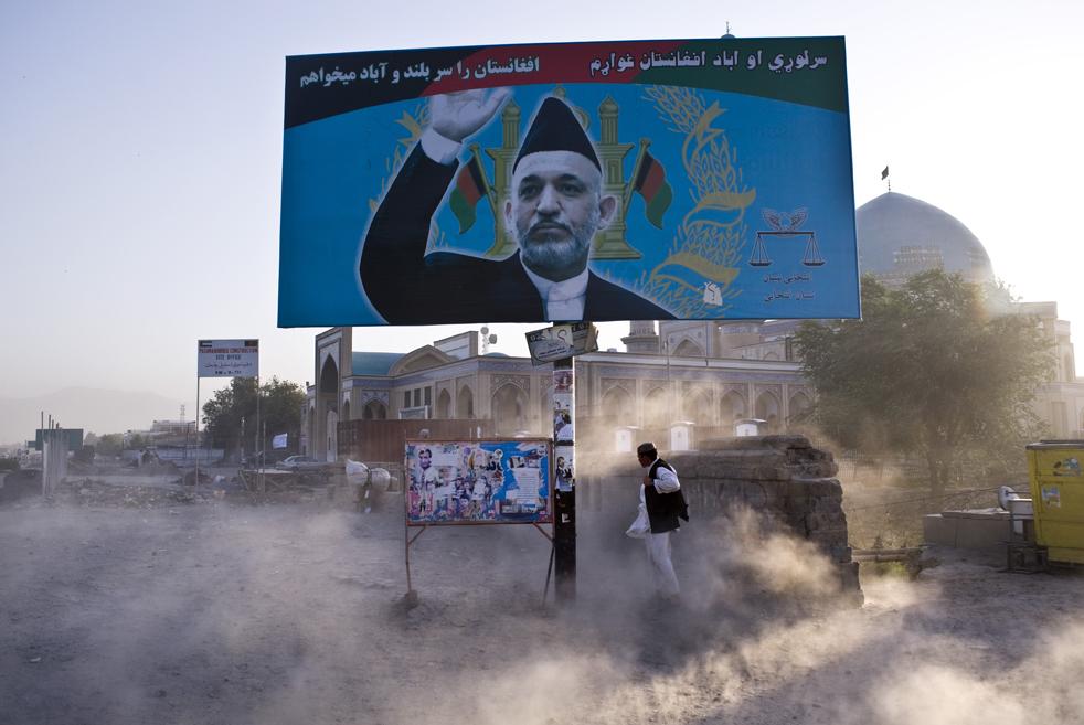 20) 20. Афганец закрывается от пыли за щитом действующего президента Хамида Карзай, одного из 41 зарегистрированных кандидатов в президенты в Кабуле 13 августа. (AFP/Getty Images/Pedro Ugarte)