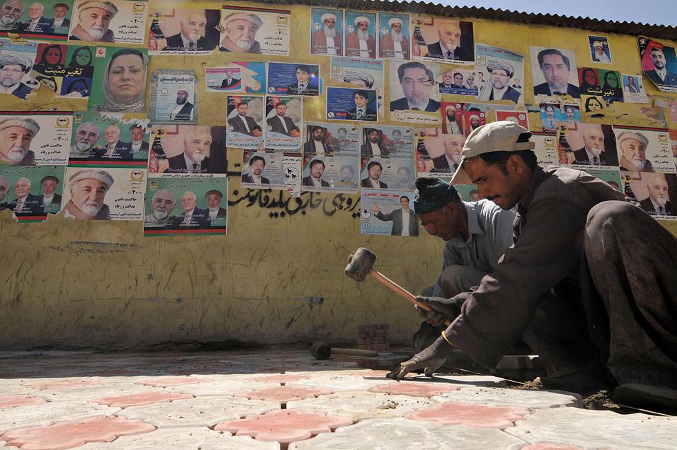21) 21. Афганские рабочие рядом со стеной с предвыборными плакатами на улице Кабула 13 августа. (AFP/Getty Images/Shah Marai)