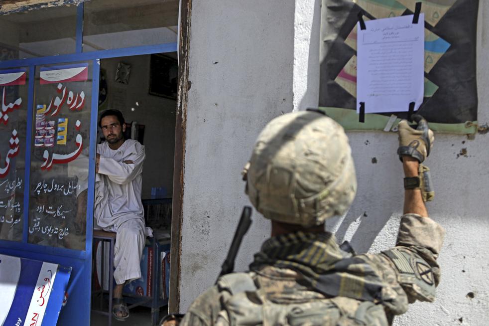 23) 23. Торговец смотрит, как 37-летний Майкл Райли из Лас-Вегаса, штат Невада, из второго батальона 87-го пехотного полка, который является частью 10-ой военной бригады горного дивизиона с базой в Форт Драме, Нью-Йорк, убирает сообщение от организации «Талибан», угрожающее всем, кто будет голосовать 20 августа в деревне Джай Зурин в провинции Вардак, в понедельник, 17 августа. (AP/David Goldman)