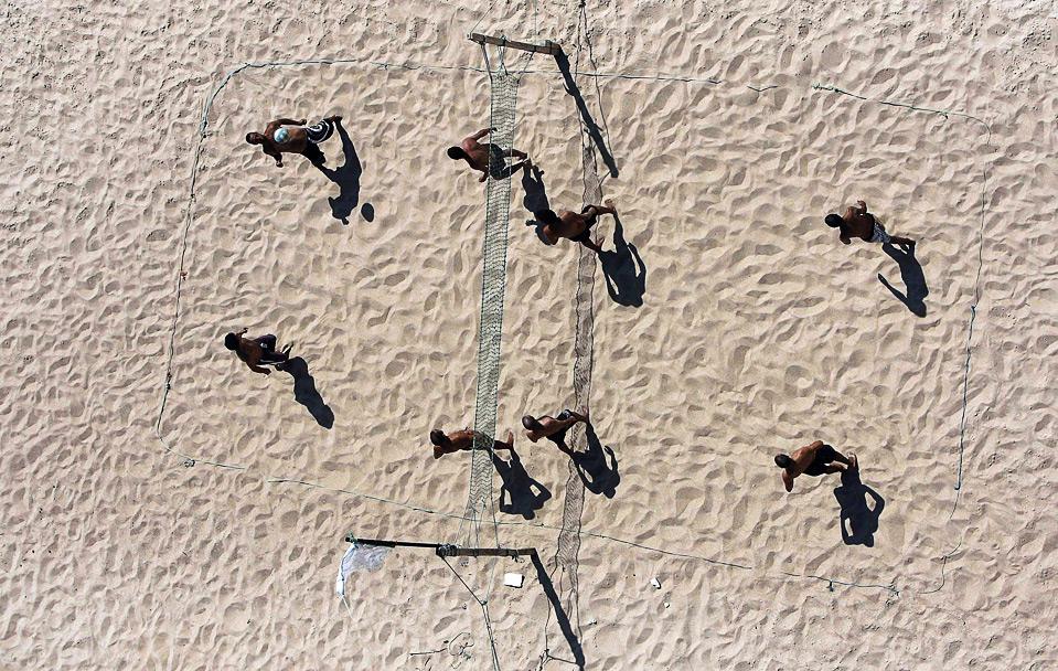 25) Люди, играют в волейбол на пляже в Пинхейро да Крус, Португалия, 8 августа. (REUTERS/Nacho Doce)