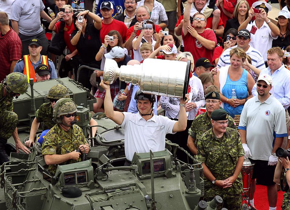 21) Игрок «Pittsburgh Penguins» Сидни Кросби поднимает над головой Кубок Стэнли, покидая канадскую военную базу Галифакс на армейской боевой машине, Новая Шотландия, 7 августа. Кросби выбрал день своего 22-го дня рождения для поездки с Кубком Стэнли. (REUTERS/Paul Darrow)