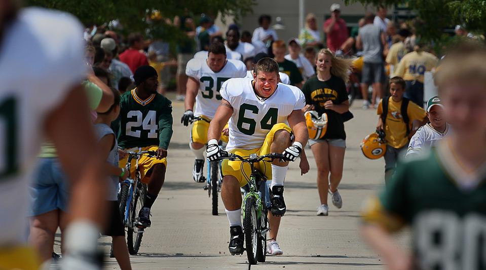 20) Дин Мухтади (в центре) из команды «Green Bay Packers» крутит педали велосипеда на тренировке, 3 августа, Грин-Бей. (Jonathan Daniel/Getty Images)