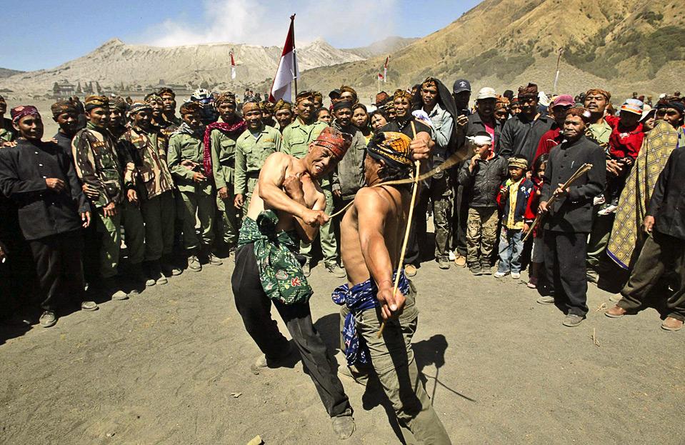 26) Члены племени Тенггер устраивают традиционные поединки на тростнике во время празднования 64-го Дня Независимости у подножия действующего вулкана, 7,641 футов высотой, в Проболинго, Индонезия, 17 августа. (AP Photo/Trisnadi)