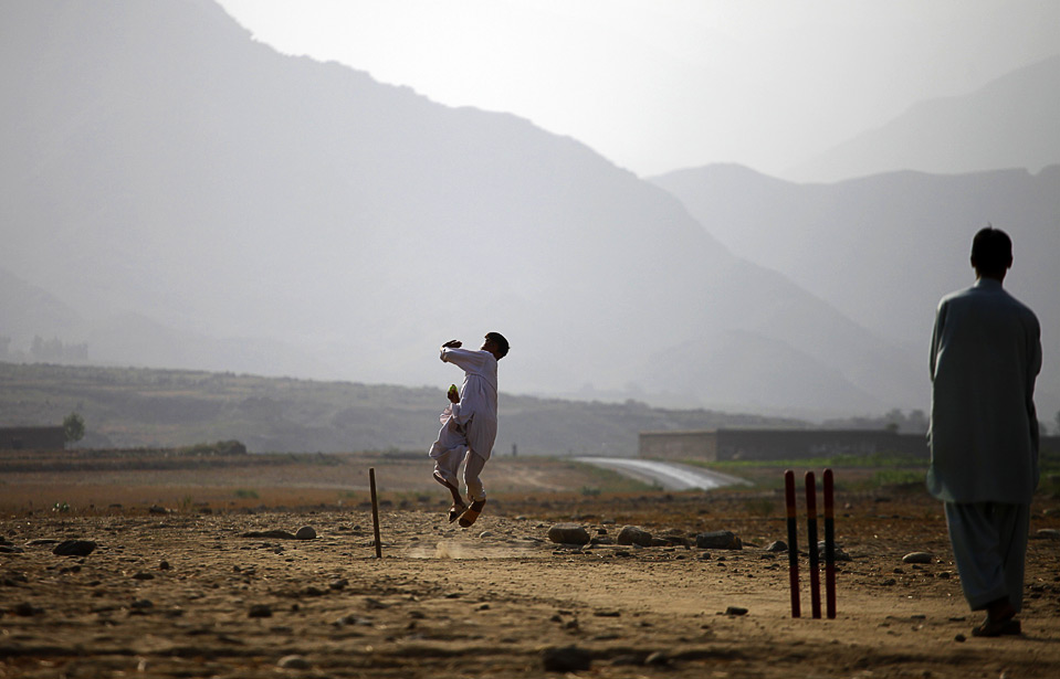 25) Афганские дети играют в крикет в долине Пеш провинции Кунар, 14 августа. (REUTERS/Carlos Barria)