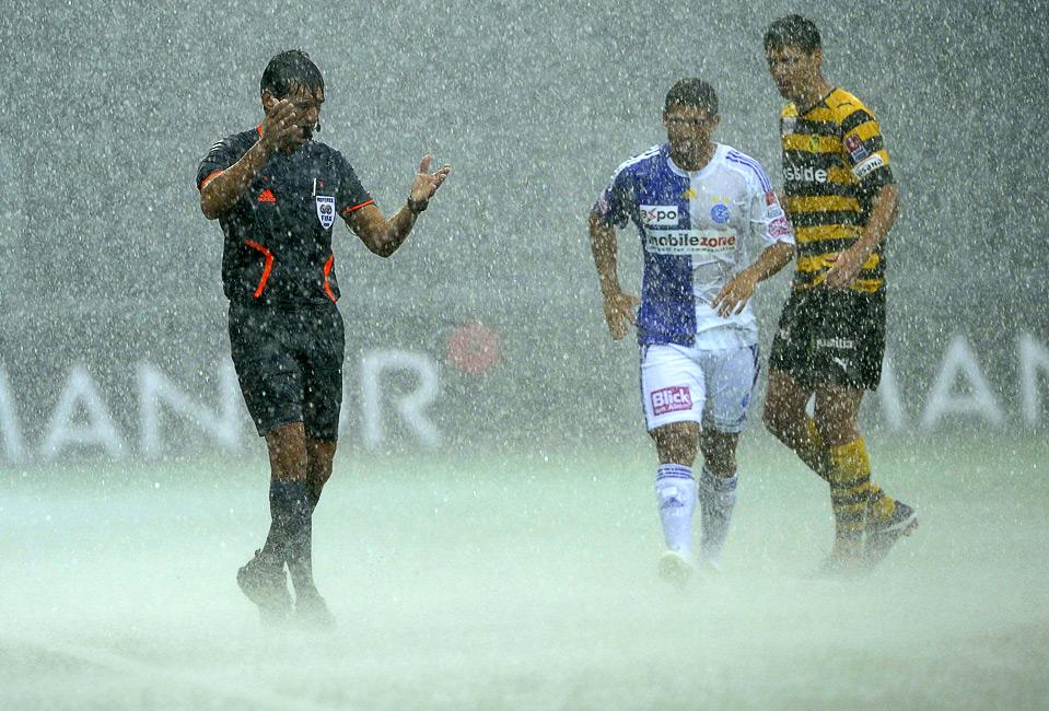 20) Судья Массимо Бусакка (слева) останавливает матч двух швейцарских команд «BSC Young Boys Bern» и «Grasshoppers Club Zurich» из-за проливного дождя, 2 августа, Берн. (AP Photo/Keystone, Marcel Bier)