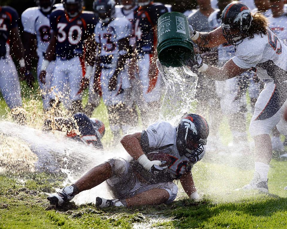 15) Бен Хамильтон обливает водой новичка «Denver Broncos» Сета Олсона после того, как тренировка превратилась в футбол в грязи, Энглвуд, Колорадо, 5 августа. (AP Photo/David Zalubowski)