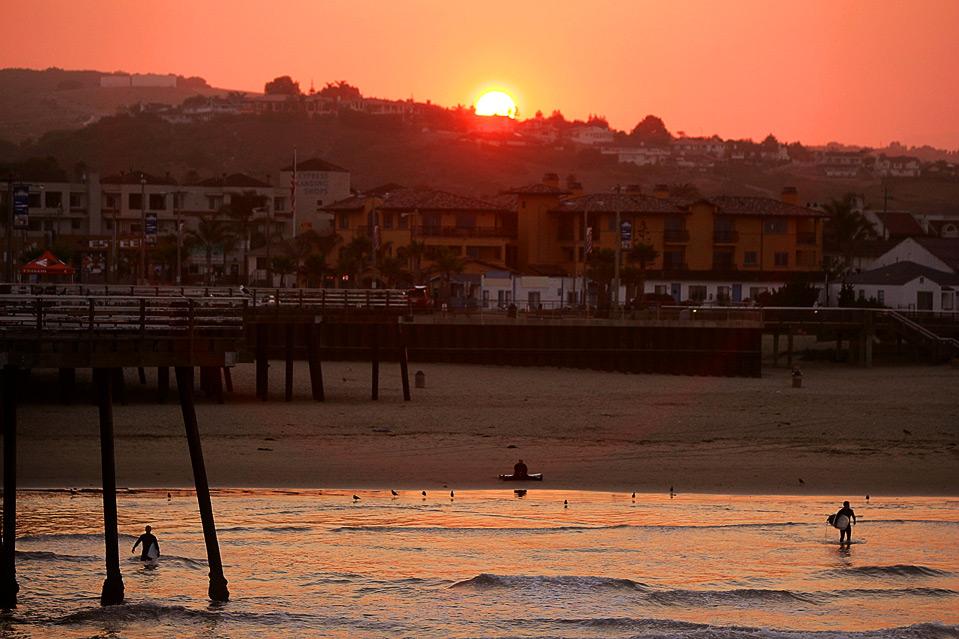 7) Местные серферы заходят в волны на закате перед началом события «Operation Restoration IV» 14 августа. (Ezra Shaw/Getty Images)