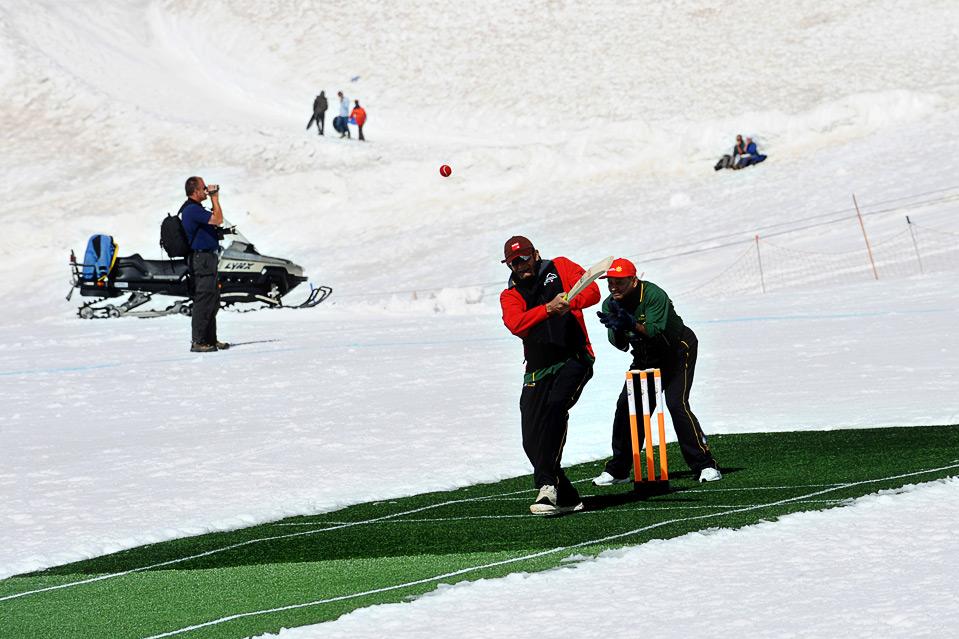 23) Сандип Патил совершает удар, в  то время как Алвин Калихаран держит воротца, во время игры в крикет на снегу на высоте 11,333 футов над уровнем моря в Бернских Альпах, Швейцария, 15 августа. (PAL PILLAI/AFP/Getty Images)