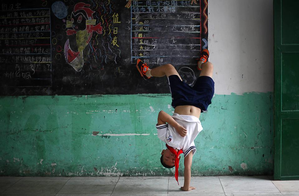 13) Ученик начальной школы в Пекине делает стойку на одной руке, 30 июля. (AP Photo/ Elizabeth Dalziel)
