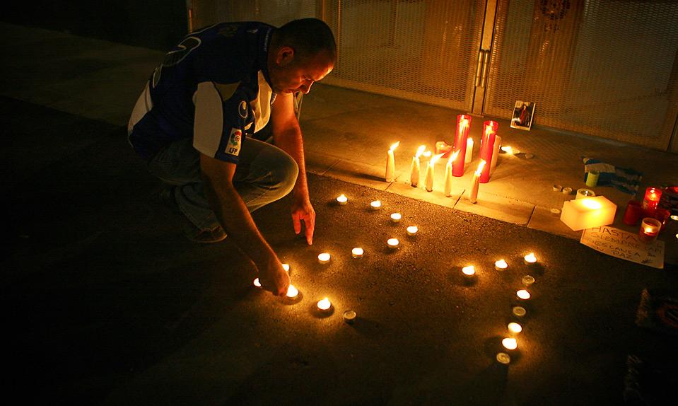 8)Болельщик «Эспаньола» зажигает свечи, выставленные в форме цифры 21, в память о капитане его любимой команды Даниэле Харке, Флоренция, 9 августа. Харке скоропостижно скончался от сердечного приступа накануне матча с командой Болоньи. Ему было всего 26 лет. (AP Photo/David Ramos)