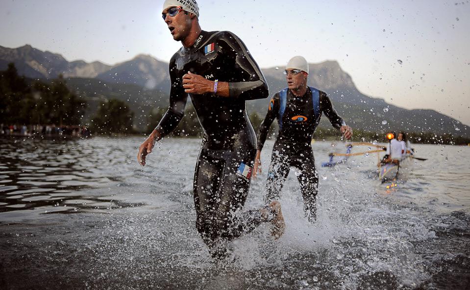 """18) Себастьян Берлир (слева) и Штефан Беилис выходят из озера в Эмбруне (Франция) 15 августа. Преодолев водный этап, длина которого составляет 3,8 км., участников одного из самых сложных соревнований - 26-го Триатлона """"Embrunman"""", впереди ожидает велогонка на 188 км. и марафон на 42 км. (JEFF PACHOUD/AFP/Getty Images)"""
