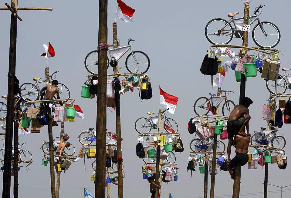 16) Добровольцы пытаются залезть на абсолютно гладкие столбы, на вершине которых висят различные призы. Этот конкурс проводится во время празднования Дня Независимости Индонезии в Джакарте 17 августа. (REUTERS/Enny Nuraheni)