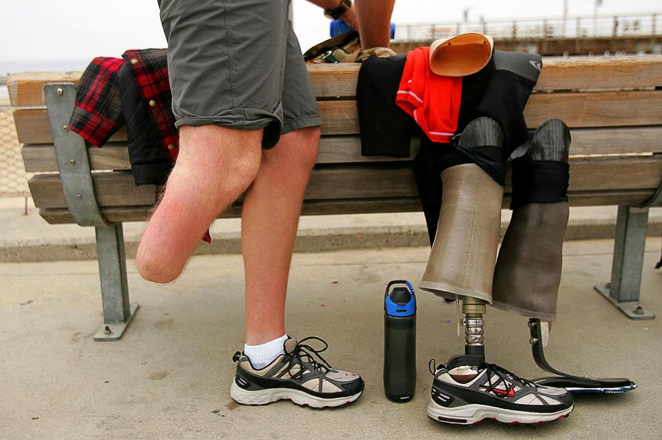 6) Серфер с ампутированной ногой Тимоти Нортон меняет свой протез на специальный для использования в воде 15 августа. Нортон был сержантом отряда, которому 1 мая 2008 года поручили очистить дома в городе Мезра, Ирак, его подстрелили, и ему пришлось ампутировать ногу. (Ezra Shaw/Getty Images)