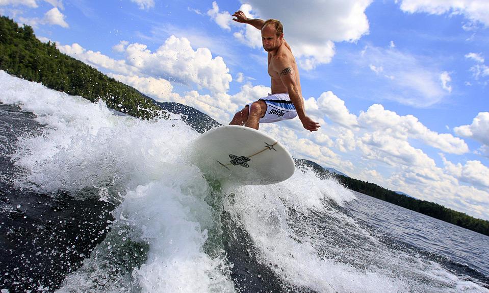 3) Олимпийский призер в состязании тобогганов-одиночек американец Брайан Мартин ловит волну, поднимающуюся за катером, на серфе, Лейк-Плэсид, 28 июля. (AP Photo/Todd Bissonette)
