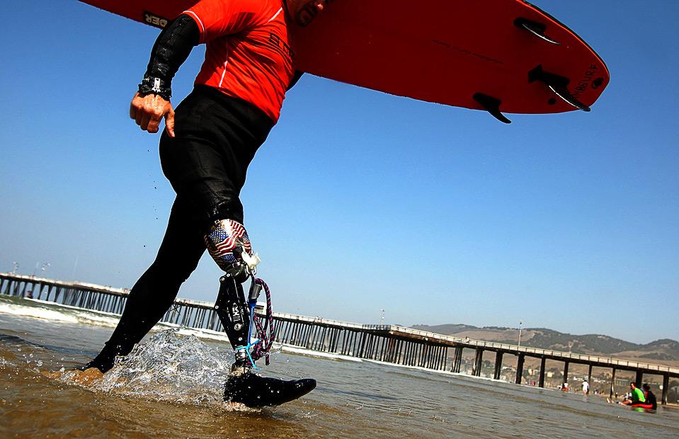 3) Бывший военнослужащий Карл Дорман из Вашингтона, округ Колумбия, несет свою доску для серфинга по пляжу 14 августа. (Ezra Shaw/Getty Images)
