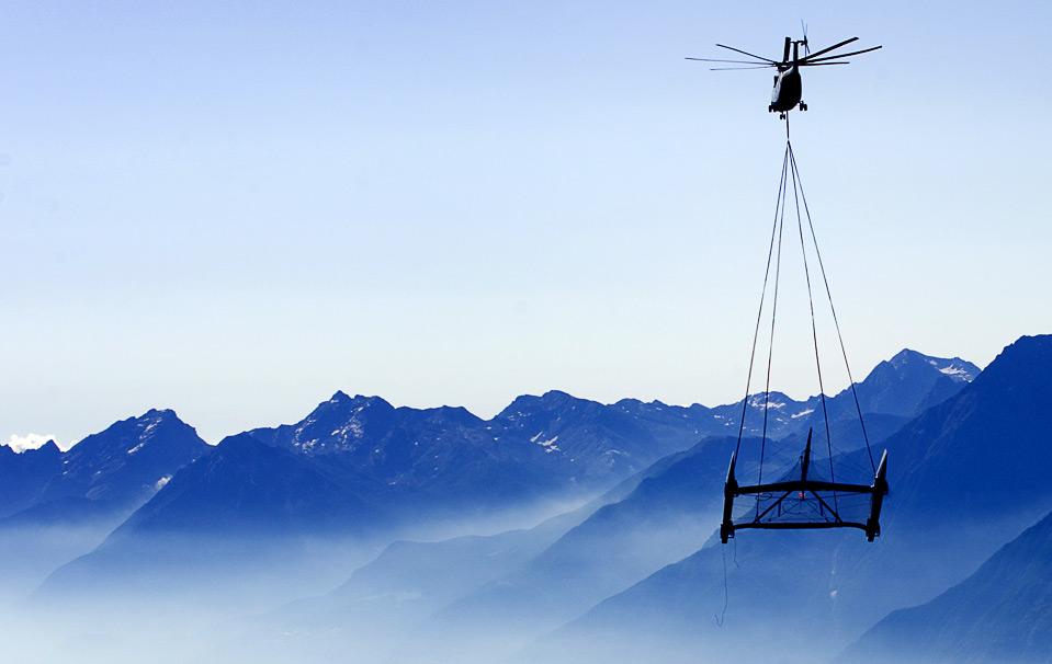 1) Катамаран команды «Alinghi» транспортируется по воздуху огромным вертолетом 7 августа. С Женевского озера, окруженного сушей, через Альпы катамаран будет доставлен к Средиземному морю. (FABRICE COFFRINI/AFP/Getty Images)