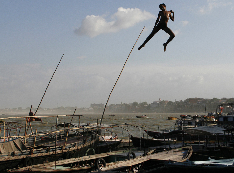 6) Мальчик спрыгивает с набережной в Гангу в городе Варанаси на севере Индии. 21 июля 2009 (REUTERS/Jayanta Shaw)