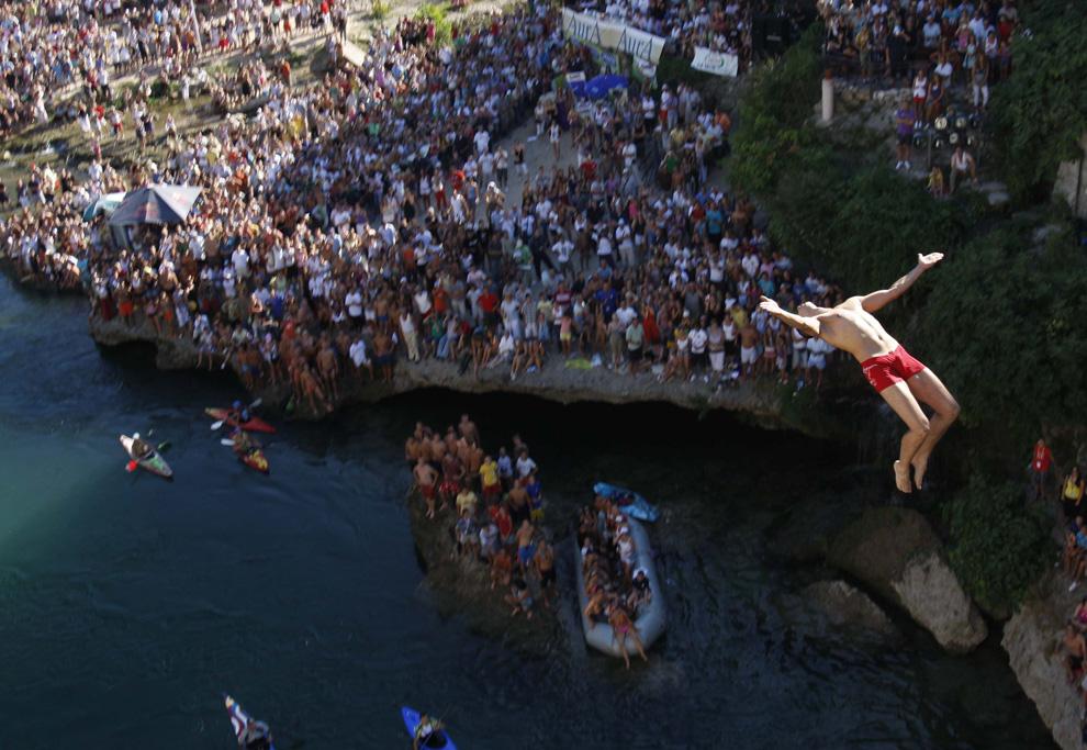 7) Дайвер прыгает в воздух во время традиционных прыжков с Мостарского Моста, расположенного в 75 км южнее Сараево, столицы Боснии. 26 июля 2009. В общей сложности в этом соревновании по прыжкам в реку Неретва с 25-метрового моста принимало участие 60 ныряльщиков. (AP Photo/Amel Emric)
