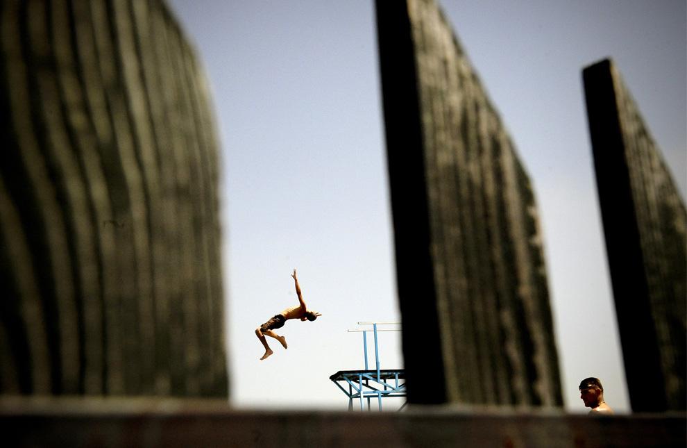 8) Температура воздуха зашкалила за 40° С, и албанец из Косово прыгает в бассейн, находящийся недалеко от деревни Милосево. 25 июля 2009. (Armend Nimani/AFP/Getty Images)