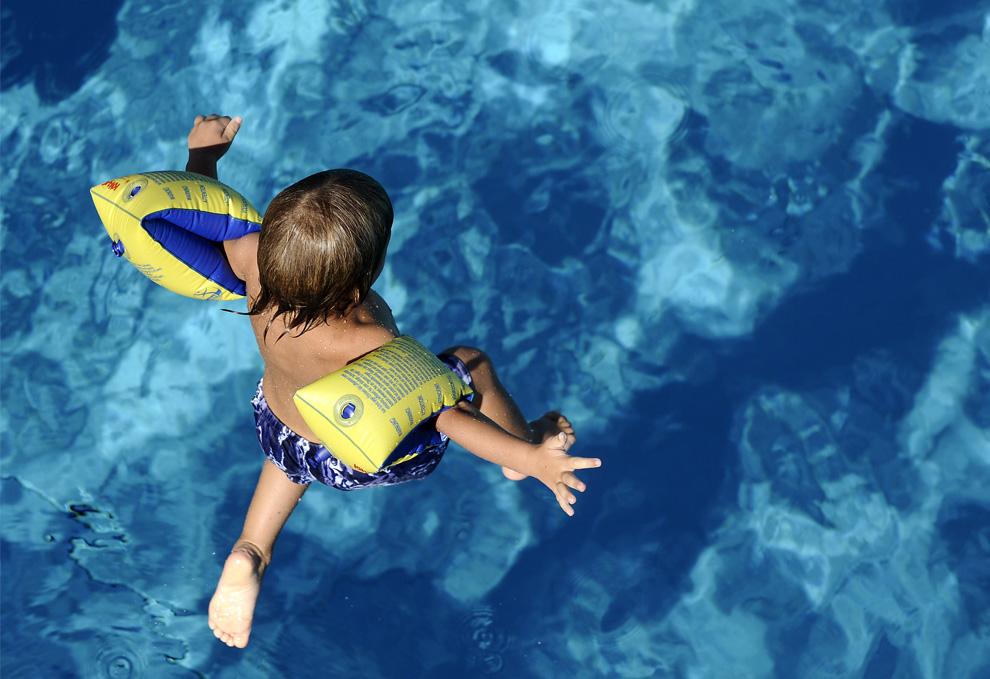 12) Мальчик с надувными подушечками для плавания прыгает в бассейн в городских купальнях «Rheinbad» в Дюссельдорфе, в понедельник 27июля 2009 (AP Photo/Mark Keppler)
