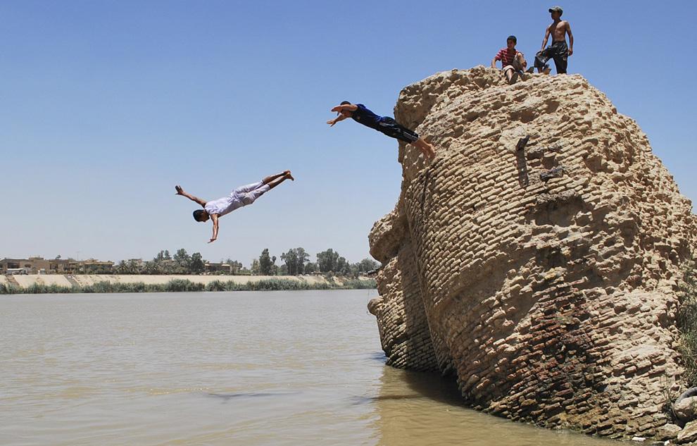 22) Мальчики прыгают с развалин строения в реку Тигр в районе Адхамия, в Северном Багдаде, 1 июля 2009 (REUTERS/Stringer)