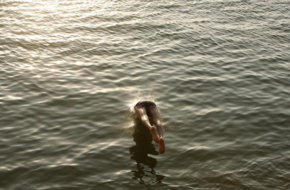 28) Жарким днем в Каире ребенок прыгает в воды реки Нил. Египет, 18 июля 2009 (REUTERS/Asmaa Waguih)