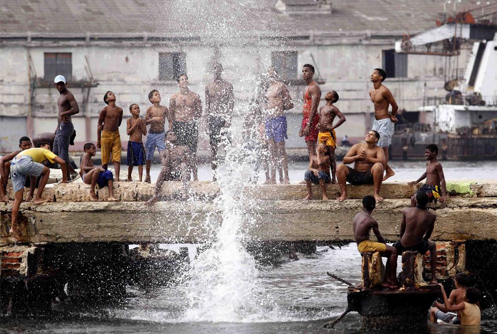 32) Мальчики соревнуются, кто выше поднимет брызги, прыгая в воду в порту Гаваны. Куба, 2 Июля 2009 (REUTERS/Desmond Boylan)