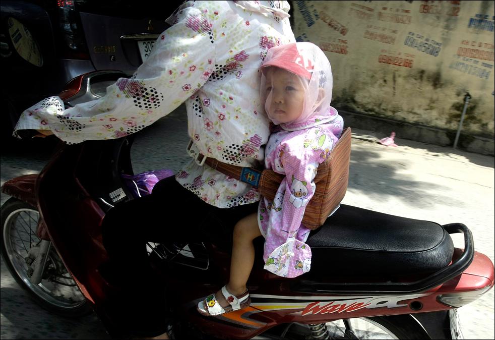 1. Ребенок с сеткой на лице от пыли и ветра едет сзади на мотоцикле в Ханое, Вьетнам, в четверг 20 августа.  (AP/Chitose Suzuki)