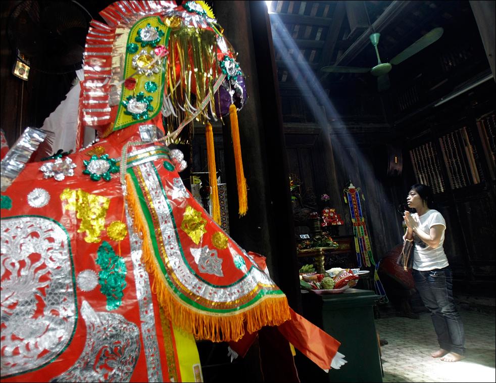 2. Женщина молится в пагоде Бо Де в округе Зялам, Ханой, Вьетнам, перед бумажной лошадью у алтаря  20 августа – в первый день июля по лунному календарю. В первый или 15-ый день лунного месяца люди часто посещают пагоды или храмы в городе Ханой, чтобы помолиться за удачу и процветание.  (AP/Chitose Suzuki)