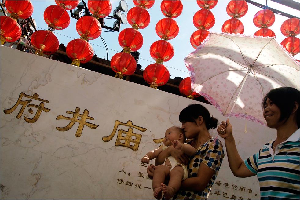 7. Китаянка успокаивает ребенка на улице Пекина, в четверг 20 августа.  (AP/Ng Han Guan)