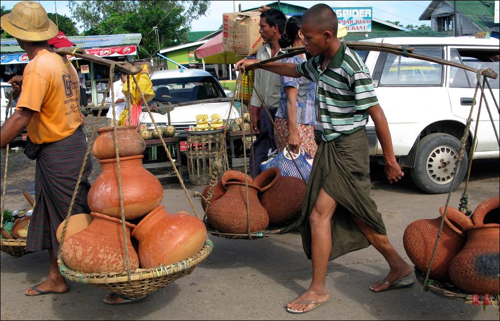 8. Бирманцы несут горшки на местном рынке в среду 19 августа в Дале, примерно в 20 км к югу от столицы  Мьянмы, Янгона.  (AP/Khin Maung Win)