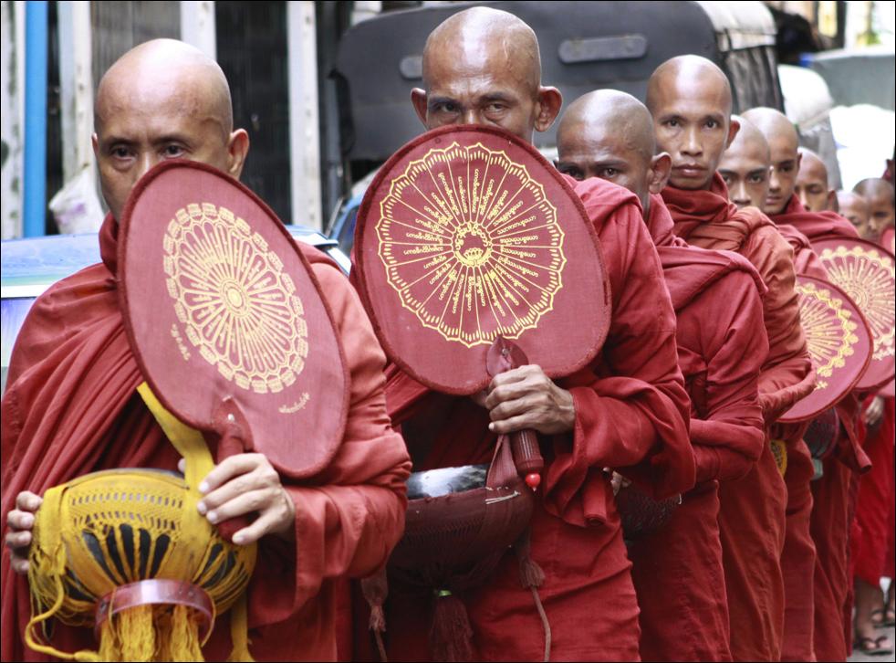 9. Группа буддистских монахов стоит в ряд в ожидании начала ежедневного процесса сбора милостыни в воскресенье 16 августа в Янгоне.  (AP)
