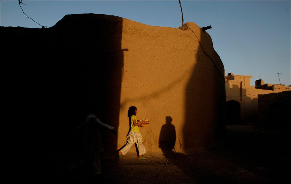 12. Девочка несет хлеб, чтобы разделить его с остальными членами семьи во время ужина в Герате, во вторник 18 августа.  (AP/Saurabh Das)