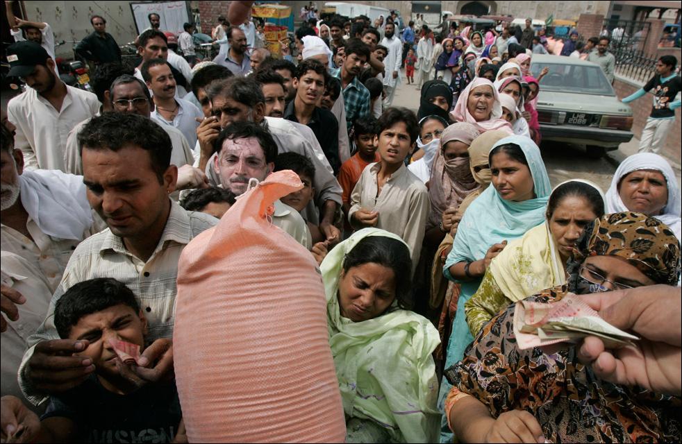 16. Пакистанские покупатели стоят в очереди за мешками с мукой, предоставленными правительством по дотации в честь предстоящего месяца Рамадана в Лахоре, Пакистан, во вторник 18 августа.  (AP/K.M.Chaudary)