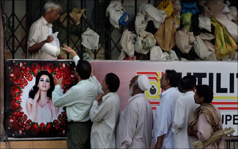 18. Пакистанцы стоят в очереди за сахаром, который выдают по дотации. Снимок сделан в Исламабаде, Пакистан, в среду 19 августа.  (AP/Anjum Naveed)
