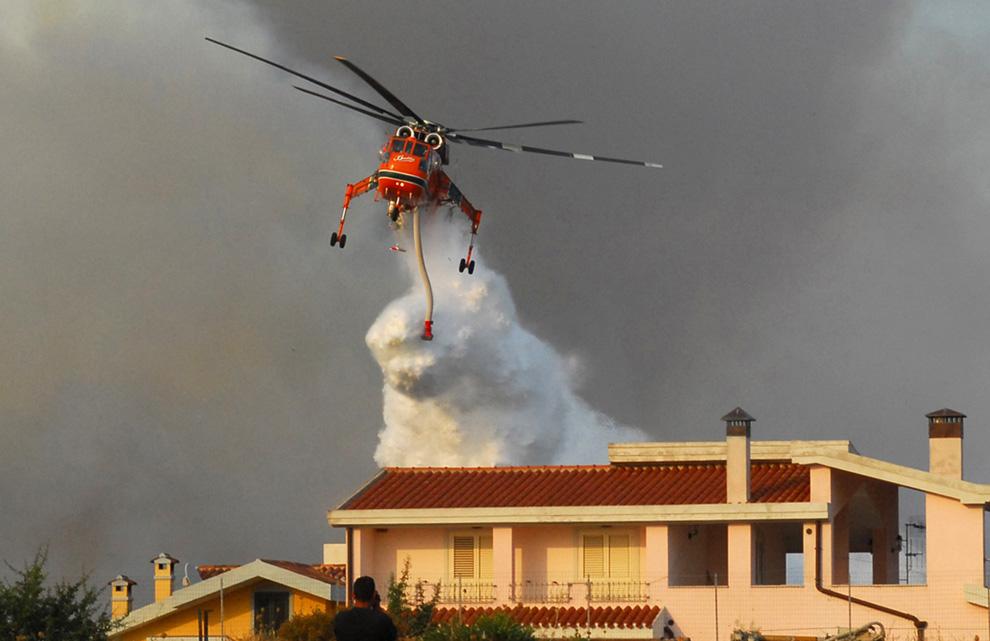 1. Вертолет пытается погасить пожар рядом с домом неподалеку от города Нуоро в центре Сардинии, Италия, 23 июля 2009 года. (MASSIMO LOCCI/AFP/Getty Images)