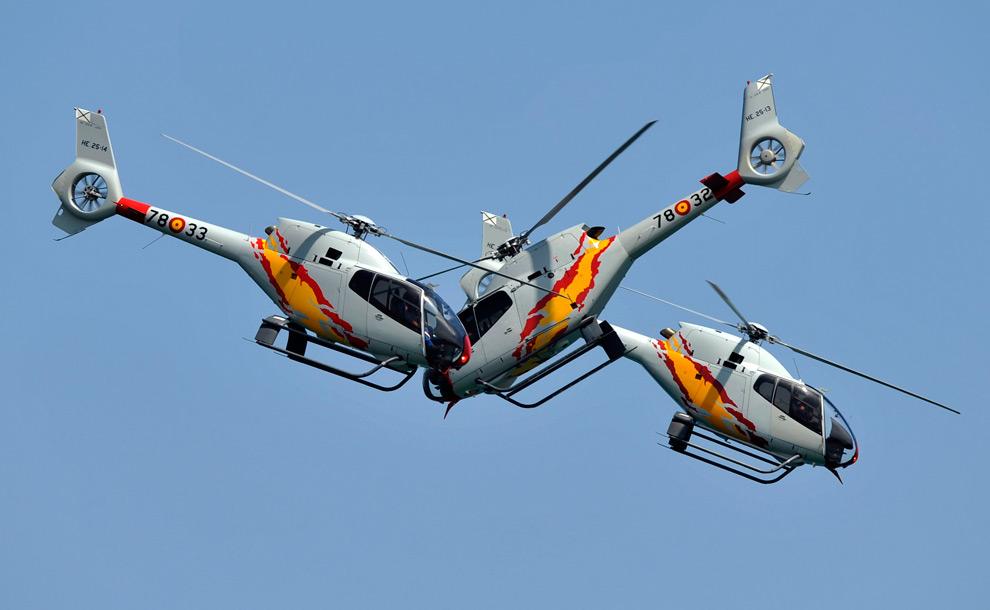 1. Вертолеты Eurocopter EC120 Colibri из пилотажной группы военно-воздушных сил Испании «Патрулла Аспа» исполняют маневр во время воздушного шоу над пляжем Сан Лоренцо в Хихоне, северная Испания, 26 июля 2009 года. (REUTERS/Eloy Alonso)