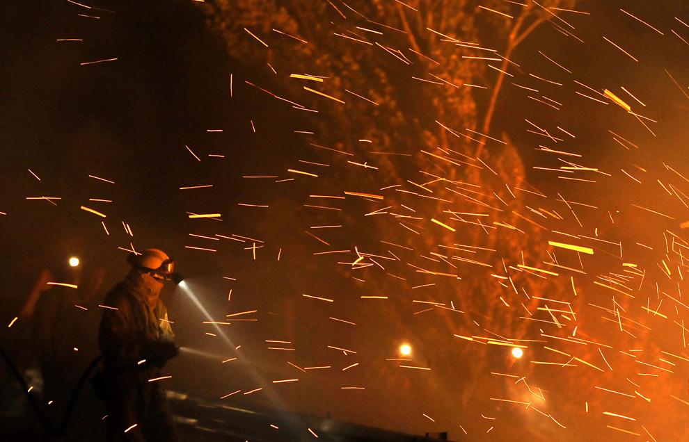 3. Искры летают вокруг одного из сотрудников пожарной бригады из города Бельчите, который сражается с огнем в Андорре утром 23 июля 2009 года неподалеку от Теруэля. Как сообщил министр обороны Карме Чакон, около полумиллиона человек боролись с разносимым ветром огнем в северо-восточной Испании 22 июля, этот пожар забрал жизни четырех пожарных. Двое человек серьезно пострадали. (PEDRO ARMESTRE/AFP/Getty Images)