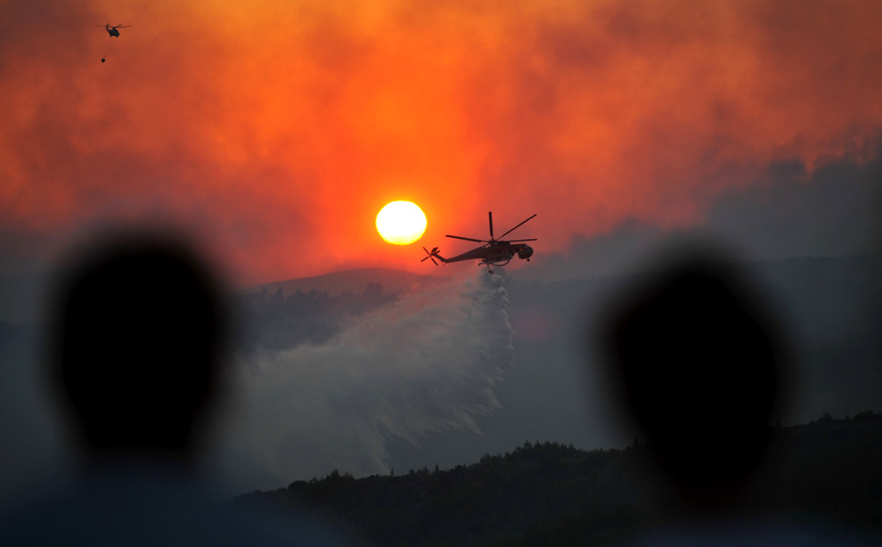 3. Жители смотрят, как противопожарный вертолет сбрасывает воду на горящий лес в Агиос Стефанос – северном пригороде Афин – в воскресенье 23 августа 2009 года. (AP Photo/Nikolas Giakoumidis)