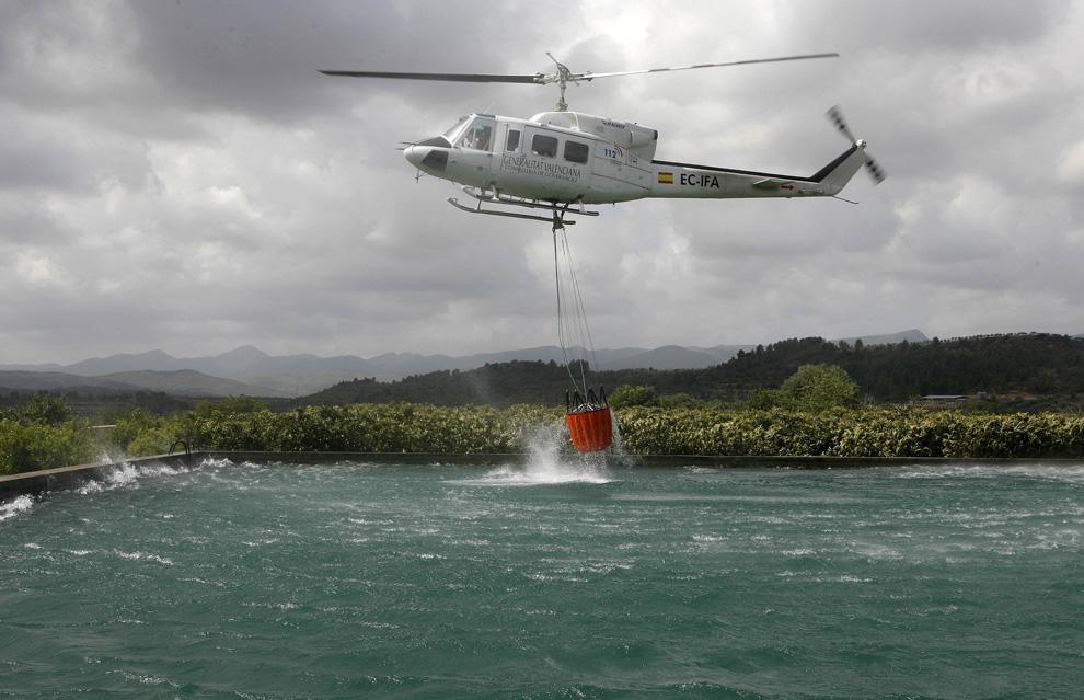 6. Спасательный вертолет собирает воду для борьбы с пожаром в Сегорбе, недалеко от Валенсии, Испания, 25 июля 2009. (REUTERS/Heino Kalis)