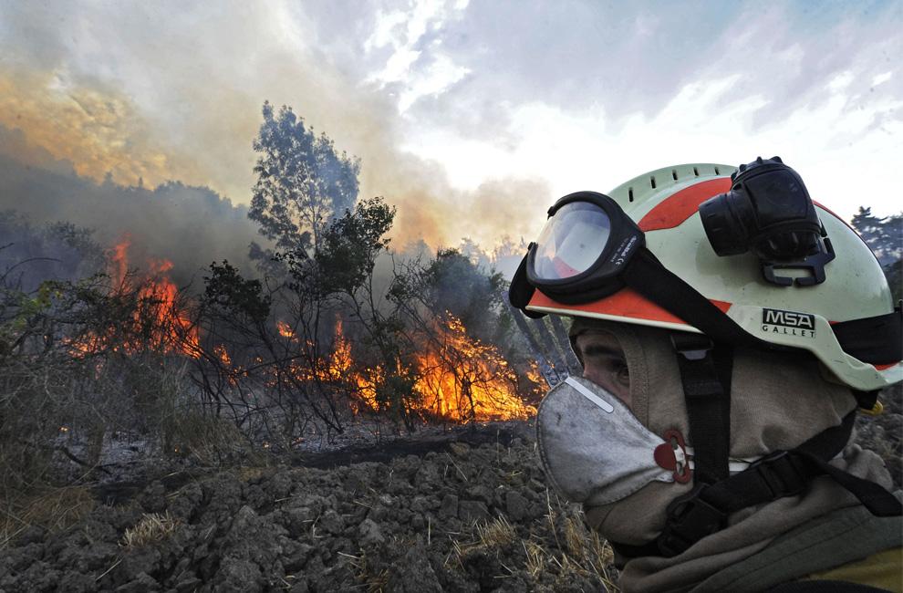 7. Пожарный проходит мимо горящей местности в Маркалайне, неподалеку от Памплоны, северная Испания, среда, 22 июля 2009 – через день после того, как погибли четыре пожарных, а еще два получили серьезные ранения в другом пожаре в Орте-де-Сан-Жоан. (AP Photo/Alvaro Barrientos)