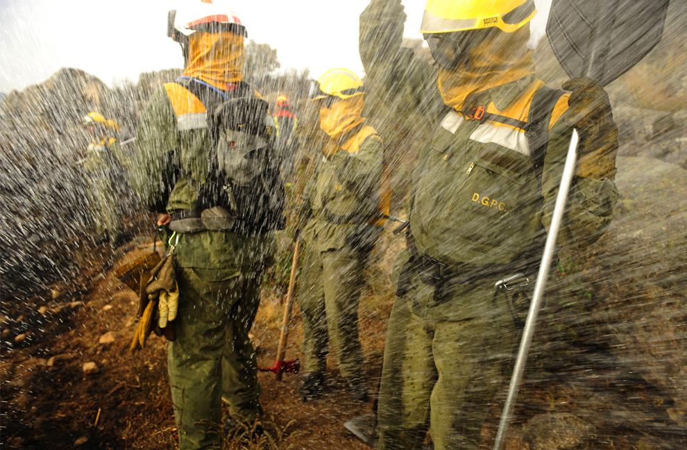 9. Пожарные прикрываются от воды, которую самолет сбрасывает недалеко от города Колладо Медиадо к северо-востоку от Мадрида, Испания, 21 июля 2009 года. Пожар стал причиной эвакуации 2 000 людей, сообщил испанской радиостанции «Cadena Ser» мэр города Мария Рубио. (PEDRO ARMESTRE/AFP/Getty Images)