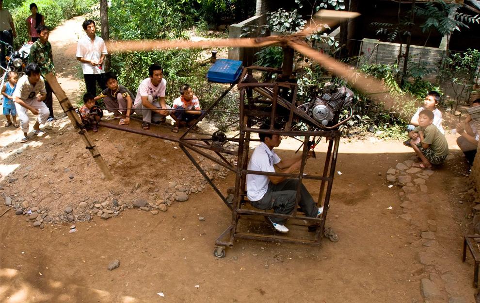 9. 22-летний фермер Ву Цхонгуань в своем самодельном вертолете в округе Джуксиань провинция Хэнань, Китай, 1 августа 2009 года. Позднее местные власти запретят Ву летать на этом вертолете из-за риска для его же безопасности. Ву строил этот вертолет, работающий на двигателе в 150 кубических см, два месяца, а затраты на его создание составили более 10 000 юань (1 460 долларов). (REUTERS/China Daily)