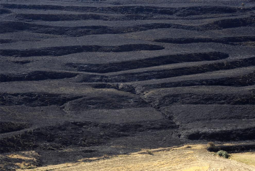 10. Сожженные поля неподалеку от Эхульве, Теруэль, Испания, 25 июля 2009. (PIERRE-PHILIPPE MARCOU/AFP/Getty Images)