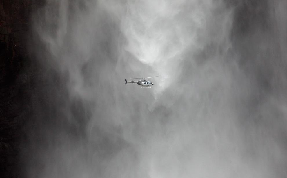 10. Вертолет с туристами летит перед водопадом Анхель – высочайшим водопадом в мире – также известным как «Сальто Анхель» в национальном парке Канайма в юго-восточной Венесуэле 23 августа 2009 года. (REUTERS/Jorge Silva)
