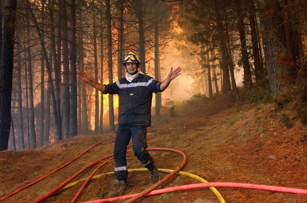 11. Пожарный запрещает проход жителям деревни Оллен на Корсике 25 июля 2009 года. Три пожара, разгоревшиеся на Корсике 23 июля, сожгли более 7 500 акров леса. (STEPHAN AGOSTINI/AFP/Getty Images)